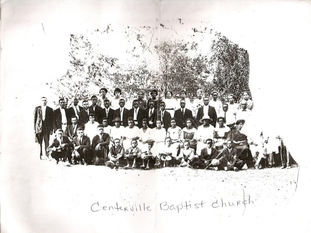 Black and white photo of a group of African American men, women, and children outside. Text written on the photo says Centerville Baptist Church.