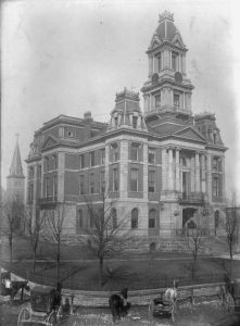 Black and white photography showing the 3rd Bourbon County courthouse. There are horses and wagons in the foreground.