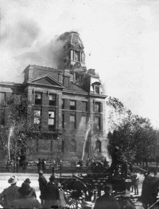 Black and white photograph showing building on fire with people watching in the foreground.