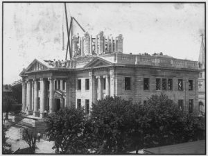 Black and white photograph showing ornate building under construction. A dome is in progress of being built.