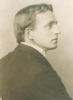 A black and white photo of a younger John Fox, Jr. He is seated in profile with his right side facing the camera.