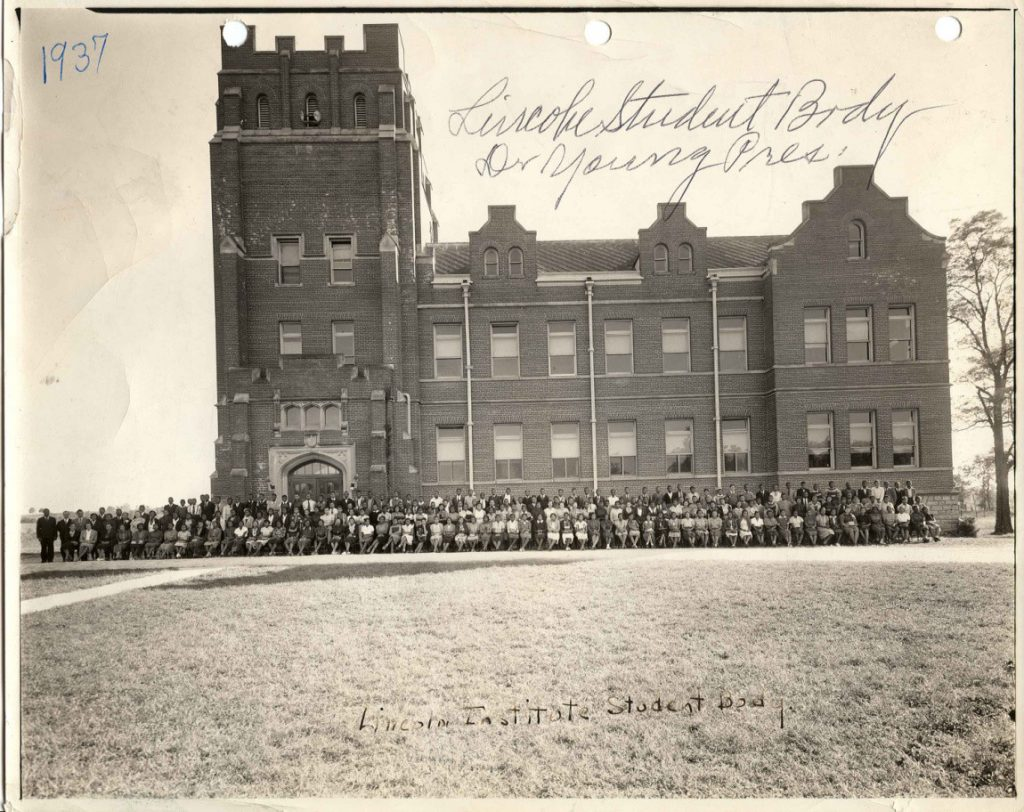 Black and white photo of a large brick building with a large group of people in front of it. Text on photo reads 1937 and Lincoln Student Body Dr. Young President.