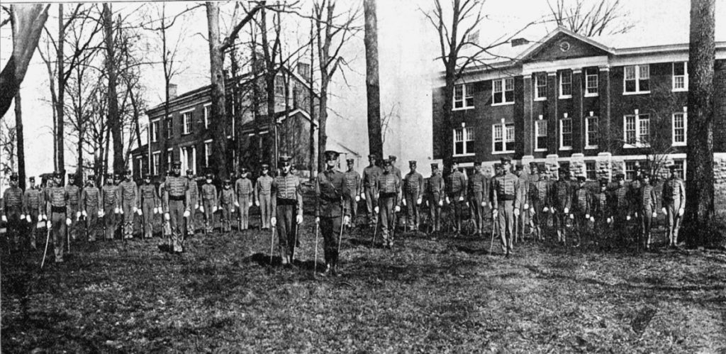 Black and white photograph of a large group of men in military dress standing in front of trees and two brick buildings.