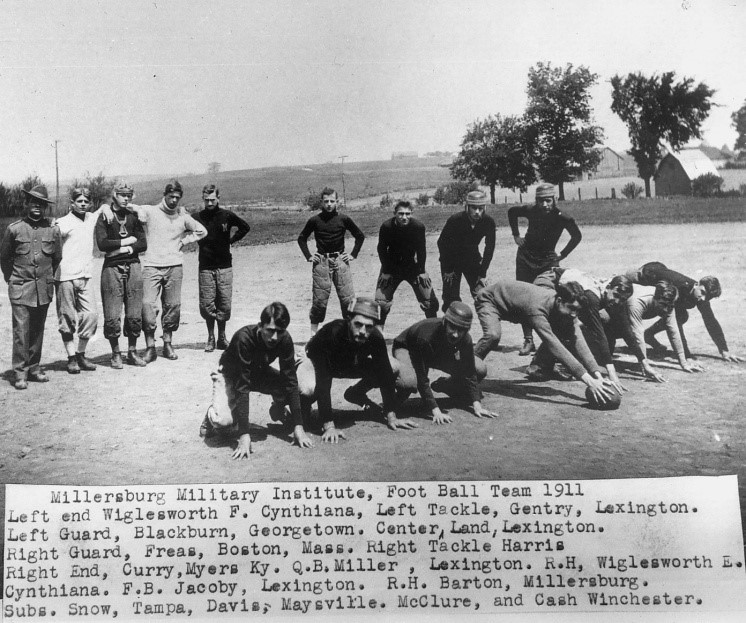 Black and white photo of 16 young men. Seven are kneeling on the ground with one man holding a football. Nine are standing in the background. Caption reads Millersburg Military Institute Football Team 1911