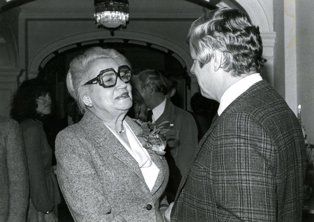 Black and white photo of Mae Street Kidd wearing glasses and talking to a gentleman in plaid suit.
