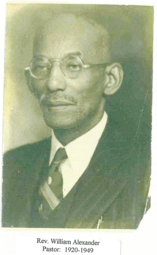 Black and white photograph of older African American man. He is wearing a suit and tie with round rimmed glasses. He is bald with a mustache.