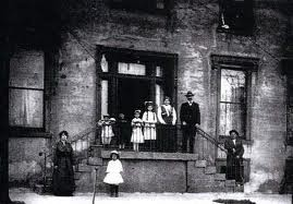 Black and white photo from the 1880s. It shows the entrance to a stone faced building. There are 4 children and 1 adult man and 1 adult woman standing at the stair landing. There is one adult male standing on stairs. There is one child in white standing in front of the landing and 1 adult woman standing to her right.
