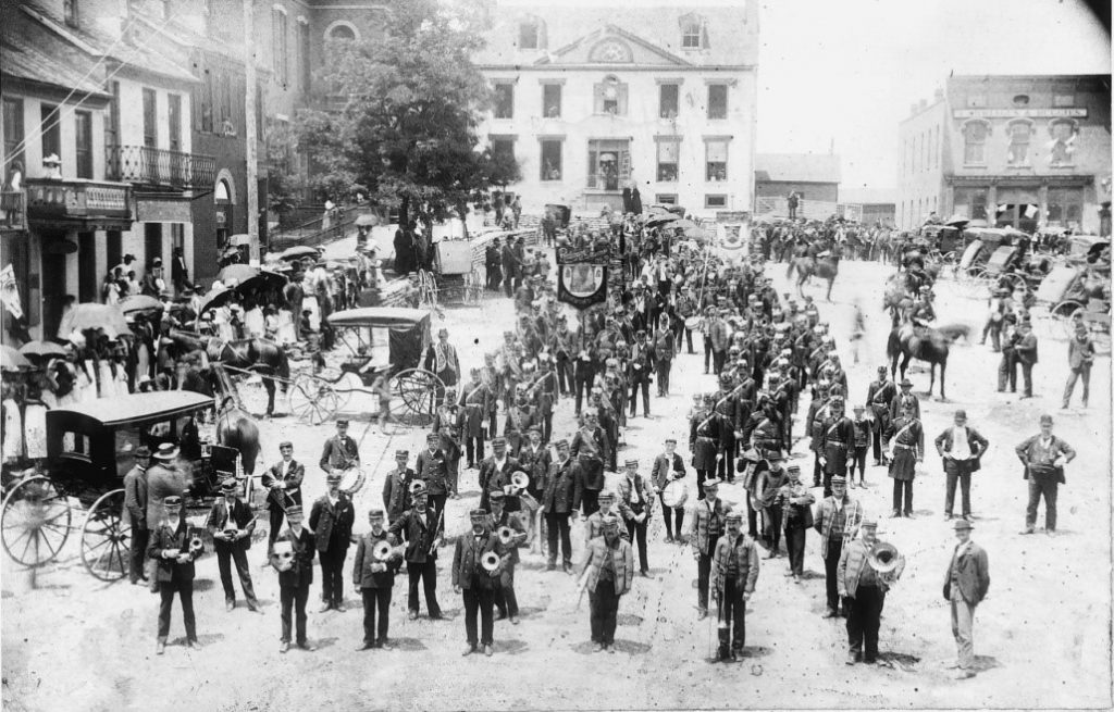 Black and white photograph showing a large group of men standing in lines. Many of the men have musical instruments. There are horses and some cars around the group.